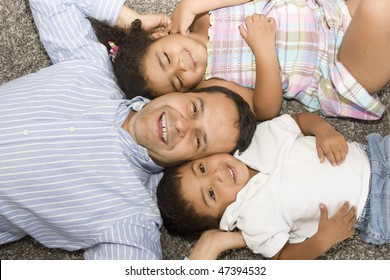 Portrait of family, dad playing with their children at home