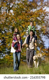 Portrait of family and dog walking through field