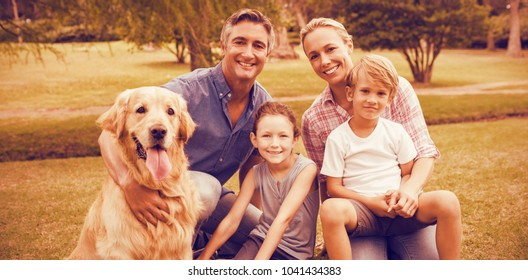 Portrait of family enjoying with dog at park on sunny day