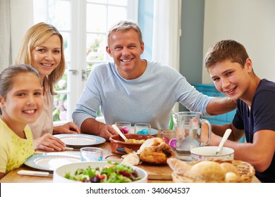 Portrait Of Family Enjoying Meal At Home Together