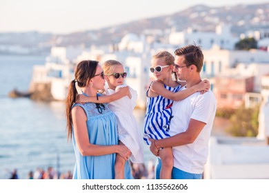 Portrait of family of four background famous little Venice in Mykonos
