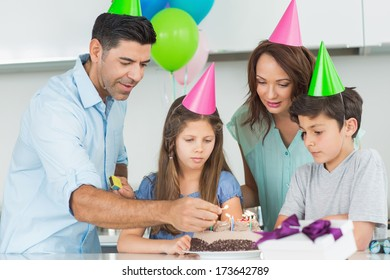 Portrait of a family of four with cake at a birthday party