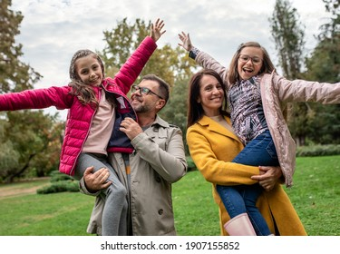 Portrait of family of four enjoying together in city park.