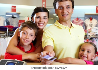 Portrait of family of four giving credit card