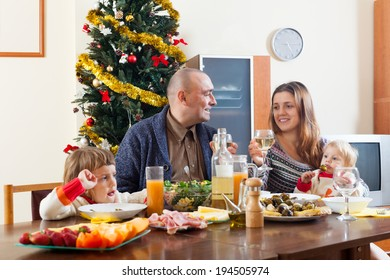 Portrait of family of four over celebratory table at home
