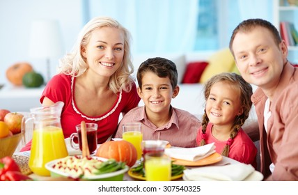 Portrait of family of four sitting at dining table