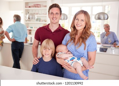 Portrait Of Family With Friends In Kitchen For Multi-Generation Party