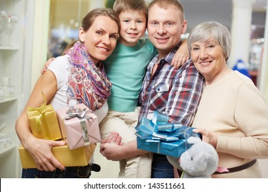 Portrait of family with gifts looking at camera in the shop