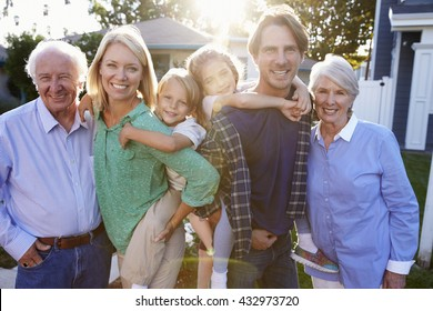 Portrait Of Family With Grandparents Standing Outside House