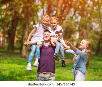 Portrait of a family having fun in a flowering city park on a bright sunny day happily spending their leisure time together outdoors