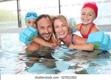 Portrait of family having fun in public indoor swimming-pool