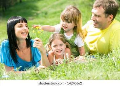 Portrait of family having rest on grass while little girl reaching for flower in womanâ??s hand
