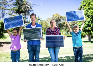 Portrait of family holding a solar panel in park