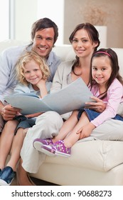 Portrait of a family looking at a photo album in a living room