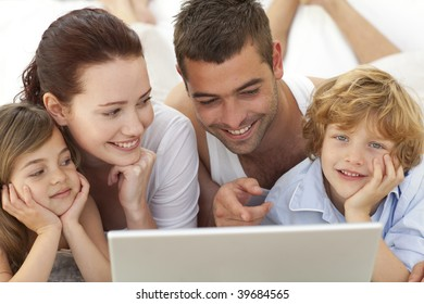 Portrait of family lying in bed using a laptop