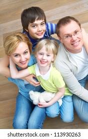 Portrait of family lying on floor in home