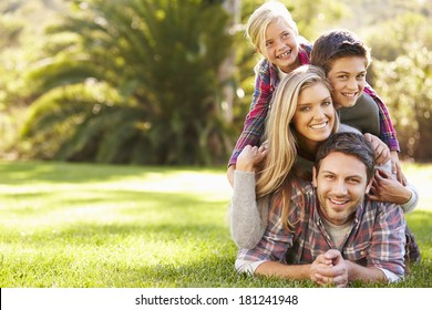 Portrait Of Family Lying On Grass In Countryside