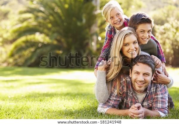 Porträt der Familie, die auf Gras auf dem Land liegt