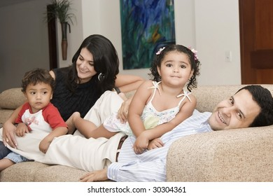 Portrait of family, mom and dad playing with their children at home