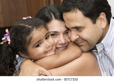 Portrait of family, mom and dad playing with their daughter at home