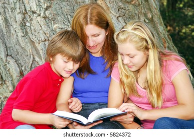 Portrait of a family - mother and children - reading a book in a park
