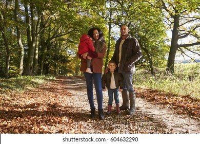 Portrait Of Family On Autumn Walk In Woodland Together