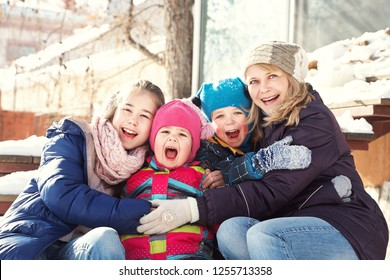 portrait of a family on the steps of a house in the winter outdoors