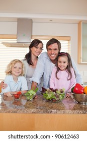 Portrait of a family preparing a salad in a kitchen