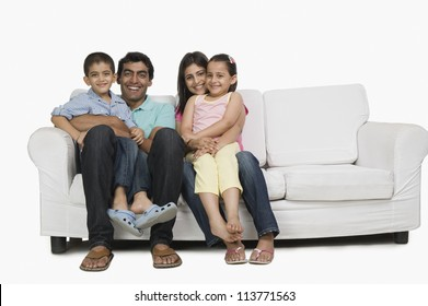 Portrait of a family sitting on a couch and smiling