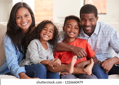 Portrait Of Family Sitting On Sofa At Home Smiling At Camera
