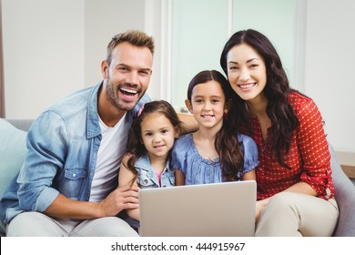 Portrait of family smiling and using laptop while sitting on sofa at home