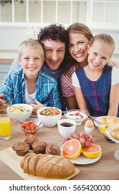 Portrait of family smiling while having breakfast at table in house