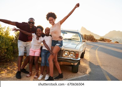 Portrait Of Family Standing Next To Classic Car