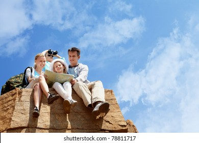 Portrait of family of travelers sitting on rocky cliff and looking at map