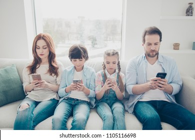 Portrait of family with two kids holding smart phones having electronic devices in hands texting sms using wi-fi 3G internet checking email searching contact. Apps concept
