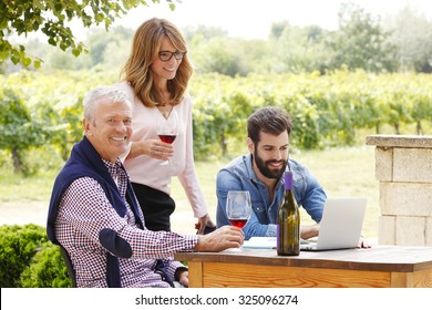 Portrait of family winemakers working together at wine estate. Professional female holding in her hand glass of red wine while senior and young winemakers working on laptop while sitting at vineyard.
