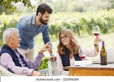 Portrait of family winemakers working together at wine estate. Middle age owner woman holding in hand a glass of red wine while consulting with senior winemaker and young sommelier. Small business.