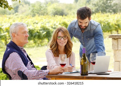 Portrait of family winery owner businesswoman sitting in front of laptop and working together with young and senior winemakers. Professional vintners tasting wine. Small business.