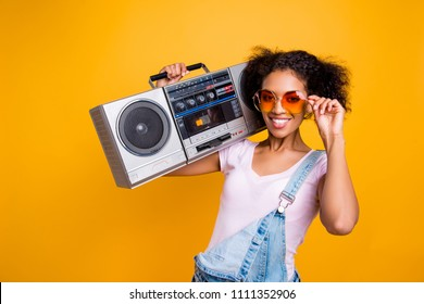 Portrait of fancy toothy girl with beaming smile in eyewear holding boom box on shoulder looking at camera isolated on yellow background. Music lover fan hobby concept