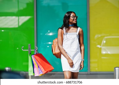 Portrait of a fantastic african american woman wearing sunglasses holds multicolored shopping bags outside the mall.