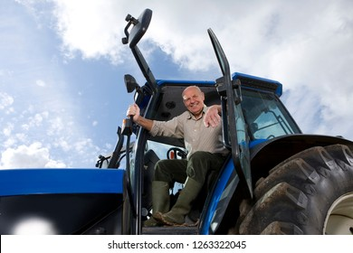 Portrait of farmer in cab driving tractor working on farm