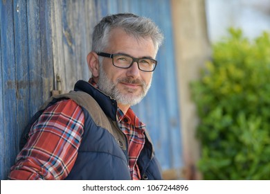 Portrait of farmer leaning on cowshed door