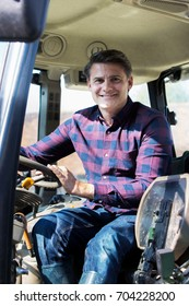 Portrait Of Farmer Sitting In Cab Of Tractor