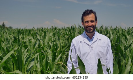 Portrait of a farmer smiling at the camera, looking and checking the cornfield, greens background. Concept: ecology, corn, bio product, inspection, water, natural products, professional, environment.