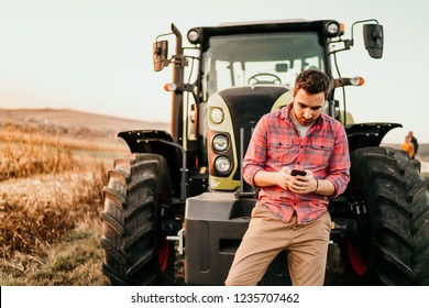 Portrait of farmer using smartphone and tractor at harvesting. Modern agriculture with technology and machinery concept