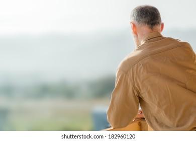Portrait : Farmer's back. Hands on handrail.