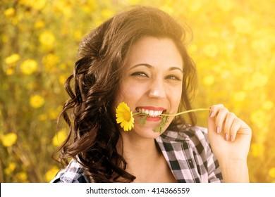 portrait of fascinating girl having fun among flowers in spring meadow