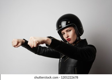 Portrait of fashion beautiful blonde girl in black leather jacket pretending to ride a motorcycle over on white background