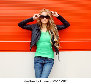 Portrait fashion beautiful woman in rock black style, wearing a sunglasses and leather jacket standing against the bright red urban wall