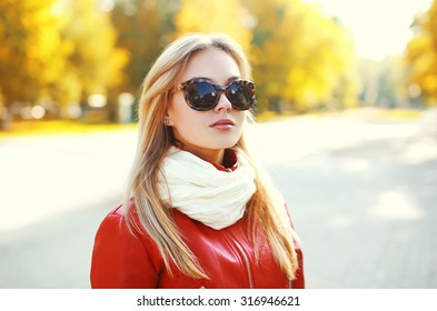 Portrait of fashion blonde woman wearing a sunglasses and red leather jacket with scarf in autumn park